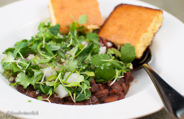 Top the chili with onions, shredded cheese, and a mix of cilantro and micro-greens