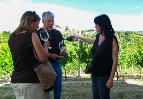 Standing in the vineyard, Leslie pours us a sample of wine from those grapes!