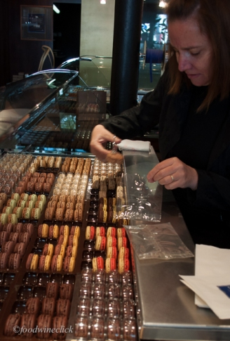 The macarons are carefully handled by special tongs