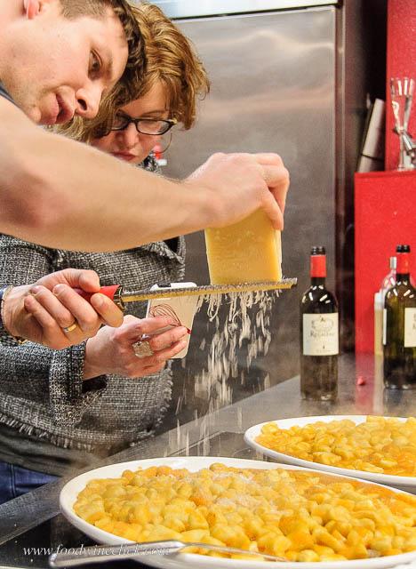 Grating Parmigiano Reggiano over fresh ricotta gnocchi