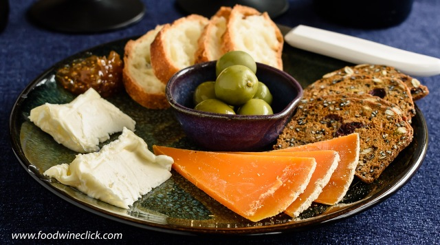 A cheese plate featuring St. Nuage and Mimolette cheeses from France