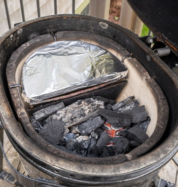 Charcoal goes on one side of the grill, ceramic diverter plate (covered with foil) sits over the empty side